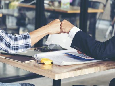 Zwei Menschen geben sich die Faust als Symbol für erfolgreiche Zusammenarbeit.